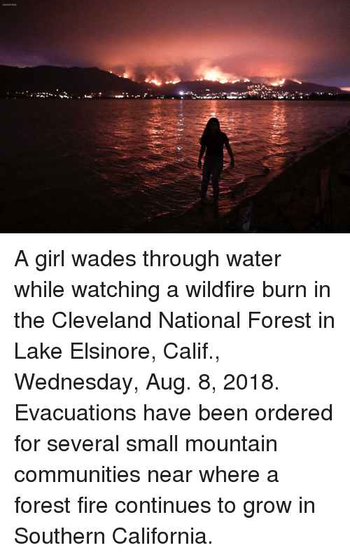 Forest Fire: A girl wades through water while watching a wildfire burn in the Cleveland National Forest in Lake Elsinore, Calif., Wednesday, Aug. 8, 2018. Evacuations have been ordered for several small mountain communities near where a forest fire continues to grow in Southern California.