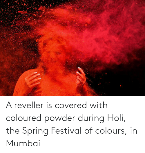 holi: A reveller is covered with coloured powder during Holi, the Spring Festival of colours, in Mumbai