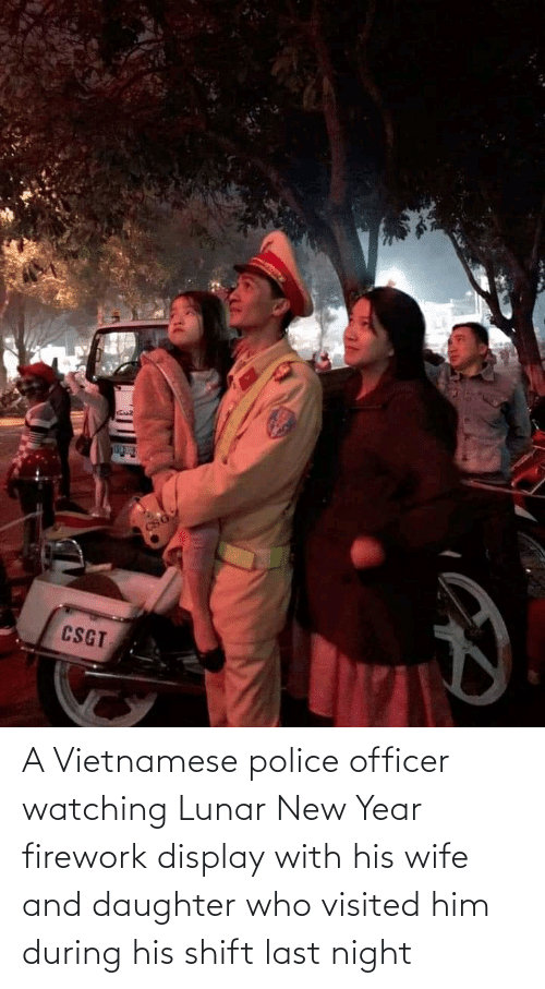 lunar new year: A Vietnamese police officer watching Lunar New Year firework display with his wife and daughter who visited him during his shift last night