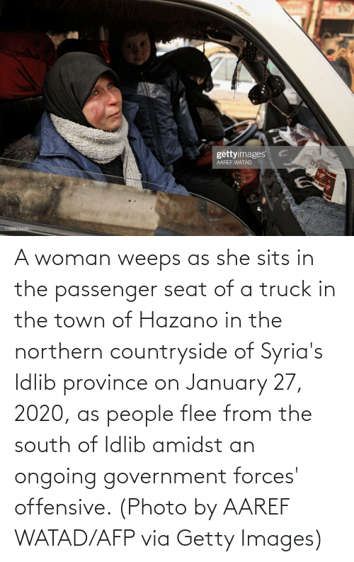 flee: A woman weeps as she sits in the passenger seat of a truck in the town of Hazano in the northern countryside of Syria's Idlib province on January 27, 2020, as people flee from the south of Idlib amidst an ongoing government forces' offensive. (Photo by AAREF WATAD/AFP via Getty Images)