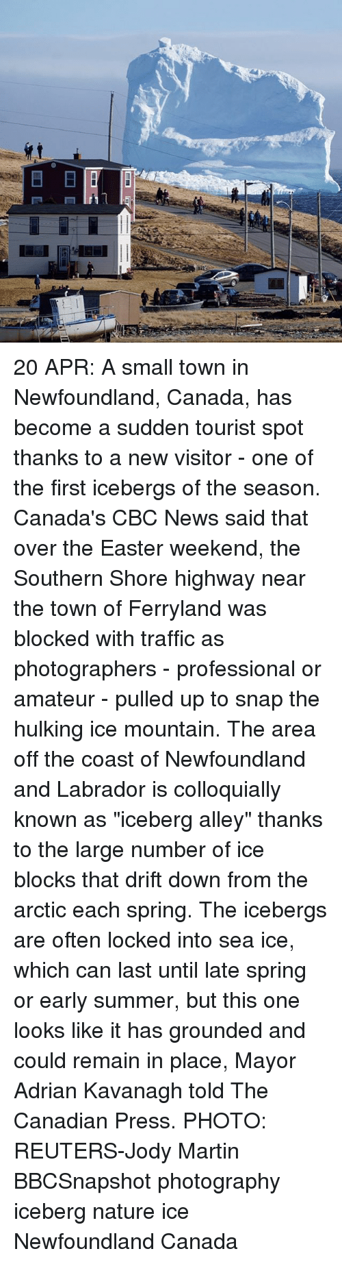 """Amateurly: E  LII 20 APR: A small town in Newfoundland, Canada, has become a sudden tourist spot thanks to a new visitor - one of the first icebergs of the season. Canada's CBC News said that over the Easter weekend, the Southern Shore highway near the town of Ferryland was blocked with traffic as photographers - professional or amateur - pulled up to snap the hulking ice mountain. The area off the coast of Newfoundland and Labrador is colloquially known as """"iceberg alley"""" thanks to the large number of ice blocks that drift down from the arctic each spring. The icebergs are often locked into sea ice, which can last until late spring or early summer, but this one looks like it has grounded and could remain in place, Mayor Adrian Kavanagh told The Canadian Press. PHOTO: REUTERS-Jody Martin BBCSnapshot photography iceberg nature ice Newfoundland Canada"""