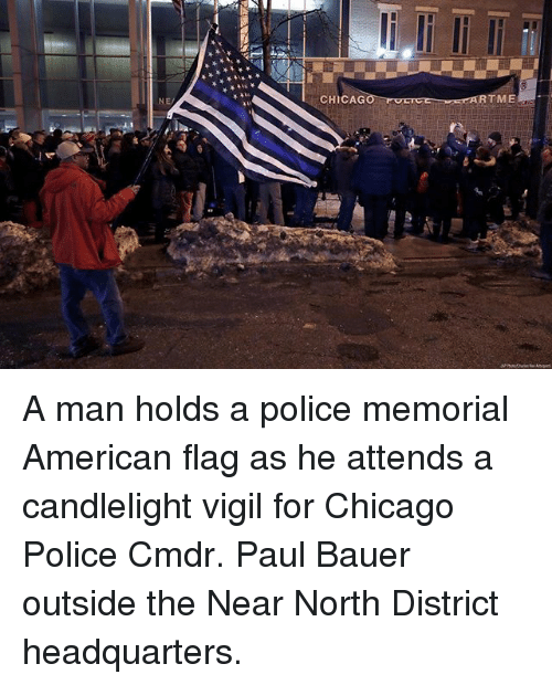 vigil: NE  CHICAG  RTME A man holds a police memorial American flag as he attends a candlelight vigil for Chicago Police Cmdr. Paul Bauer outside the Near North District headquarters.