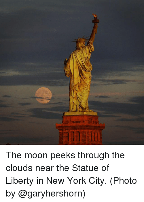 Mooned: The moon peeks through the clouds near the Statue of Liberty in New York City. (Photo by @garyhershorn)