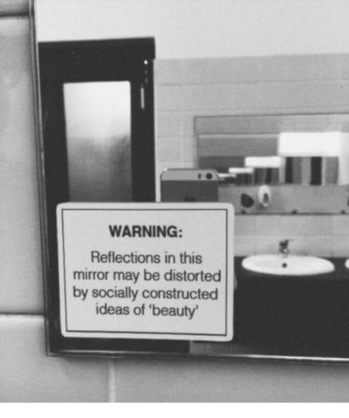 Reflections: WARNING  Reflections in this  mirror may be distorted  by socially constructed  ideas of 'beauty