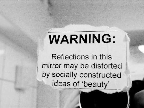 Reflections: WARNING:  Reflections in this  mirror may be distorted  |by socially constructed  ideas of 'beauty